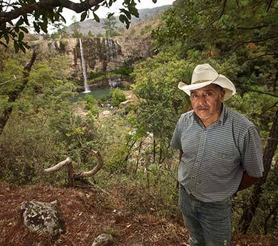 Roberto, a member of CABRIPEL, stands at a waterfall in the cooperative's land.