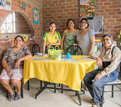 A banana-farming family enjoying their new home at the Fairtrade certified APBOSMAM cooperative, Peru.